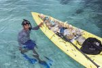 A diver from Wakatobi's cleaning team removes plastics and other rubbish found underwater